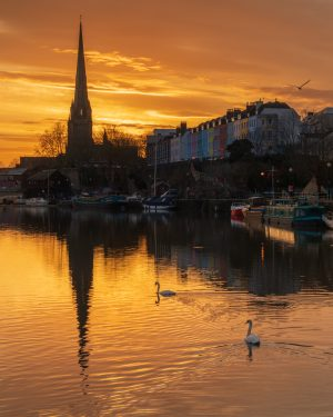A fine art cityscape print of sunrise with swans at St Mary Redcliffe in Bristol